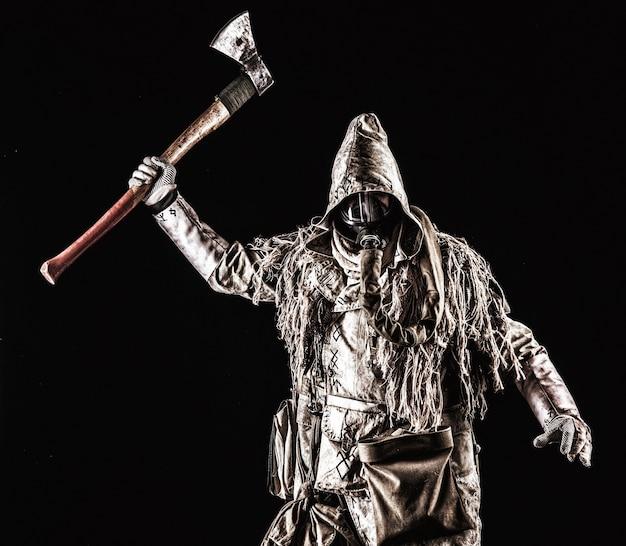 Survivant post-apocalyptique, harceleur de zone radioactive, tueur en série fou ou maniaque en masque à gaz et vêtements en lambeaux décorés de runes, menaçant avec une hache levée isolée sur un tournage en studio noir