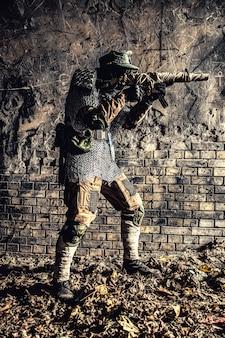 Survivant post-apocalyptique, soldat de la troisième guerre mondiale, partisan ou harceleur du conflit nucléaire mondial, dans une casquette militaire et un gilet pare-balles fait à la main avec une mitraillette enveloppée dans un bunker ou une mine abandonné