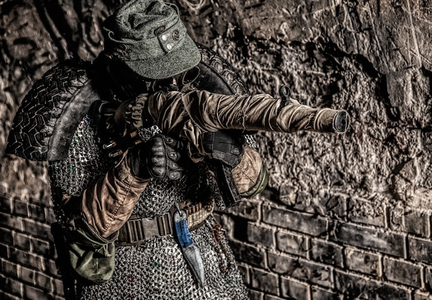 Survivant Post-apocalyptique, Soldat De La Troisième Guerre Mondiale, Partisan Ou Harceleur Du Conflit Nucléaire Mondial, Dans Une Casquette Militaire Et Un Gilet Pare-balles Fait à La Main Avec Une Mitraillette Enveloppée Dans Un Bunker Ou Une Mine Abandonné Photo Premium
