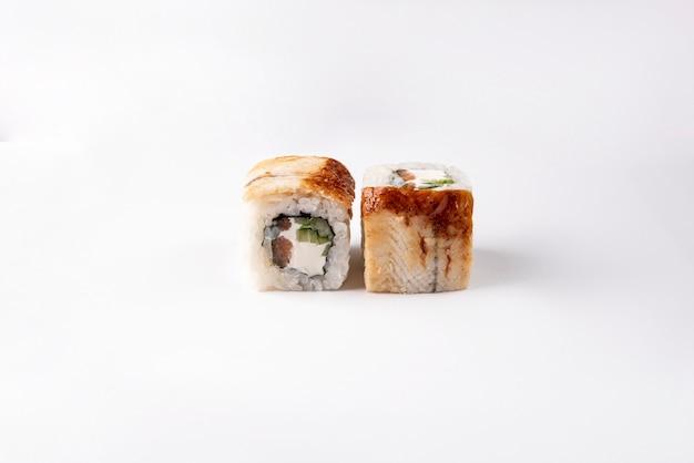Sushi avec anguille fumée, fromage de philadelphie, concombre, thon et sésame avec sauce unagi sur un espace blanc