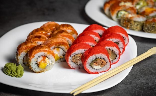 Sushi sur une assiette blanche. un ensemble de rouleaux avec du wasabi et des bâtons en bois.