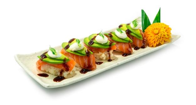 Sushi au saumon nigiri sur l'avocat et la sauce japonaise sideview style alimentaire