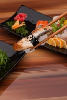 Sushi sur des baguettes se bouchent sur un fond de plats de sushi