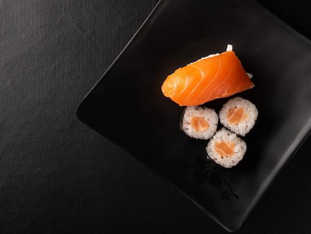 Sushi, bel arrangement de sushi fait sur une plaque noire sur une surface sombre