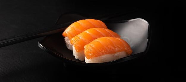 Sushi, bel arrangement de sushi avec hashi fait sur une plaque noire sur une surface sombre