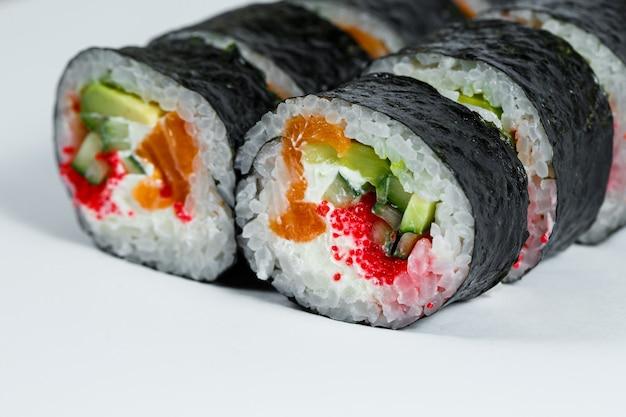 Sushi De Cuisine Japonaise En Feuille De Nori Avec Avocat, Poisson Frais Et Caviar Rouge Sur Plaque Blanche Photo Premium