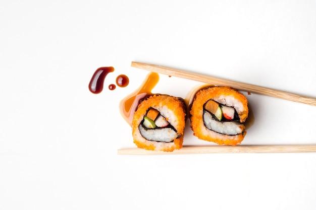 Sushi, cuisine japonaise, rouleau de californie avec des baguettes et sauce sur fond blanc.