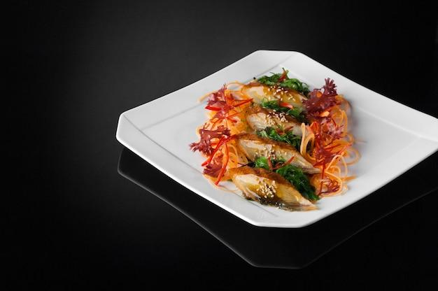 Sushi dans une assiette blanche sur fond sombre avec reflet