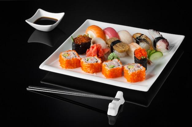 Sushi dans une assiette blanche avec pot de sauce et baguettes sur fond noir avec reflet