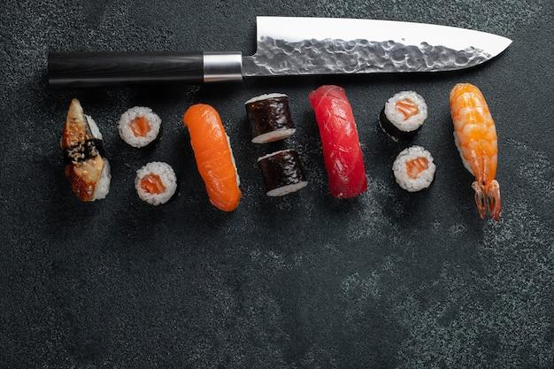 Sushi différents avec un couteau japonais sur du béton.