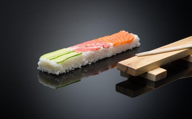 Sushi sur fond noir avec des baguettes. forme de presse en bois pour faire des sushis