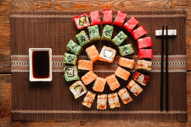 Sushi japonais, art culinaire. grand ensemble de petits pains frais servis en spirale colorée sur un tapis de paille marron, à plat. photo de menu de restaurant de luxe, cuisine orientale traditionnelle.