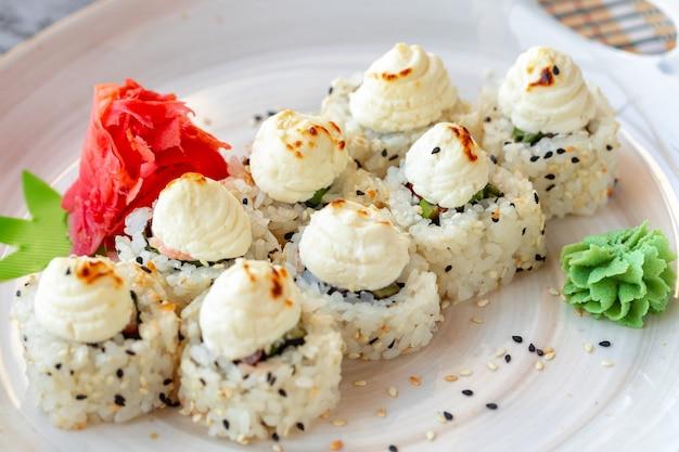 Sushi japonais aux graines de sésame et glaçage à la crème sur fond gris