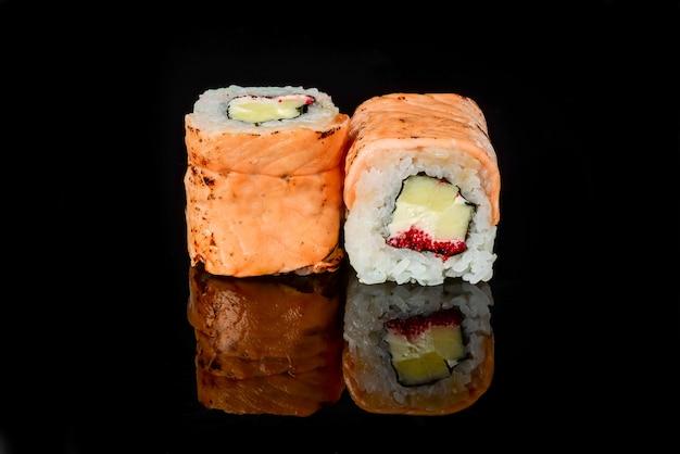 Sushi japonais frais traditionnel roule sur un fond noir