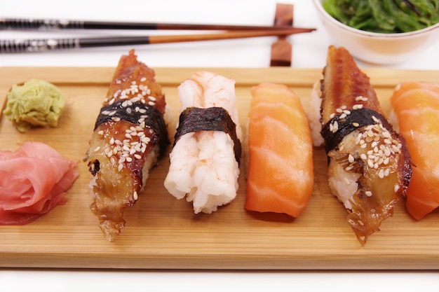 Sushi japonais sushi set sur plateau en bois servi avec sauce soja au gingembre et salade d'algues sushi rolls saumon nigiri crevettes nigiri unagi nigiri