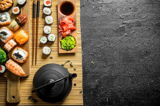 Sushi japonais traditionnel, maki et rouleaux sur serviette sur table rustique