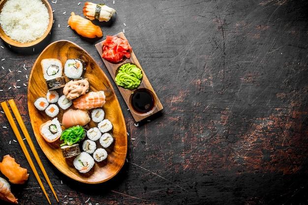 Sushi japonais traditionnel et rouleaux avec sauce soja et gingembre. sur table rustique sombre