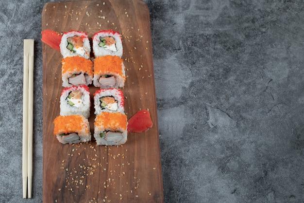 Sushi maki au caviar rouge et fromage à la crème sur une planche de bois.