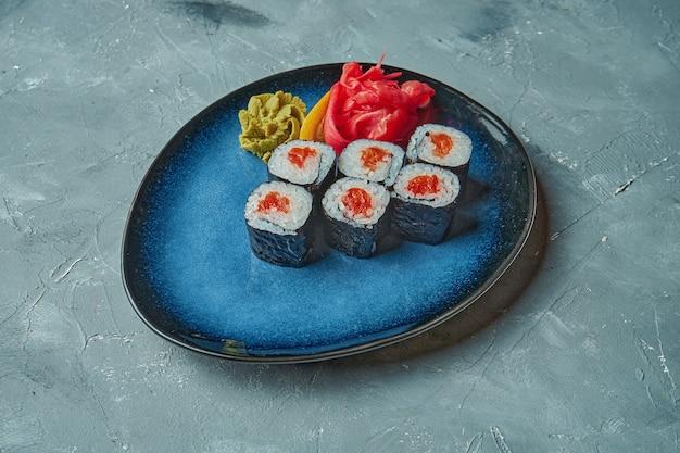 Sushi maki roll au saumon sur une assiette bleue sur une surface grise. cuisine japonaise