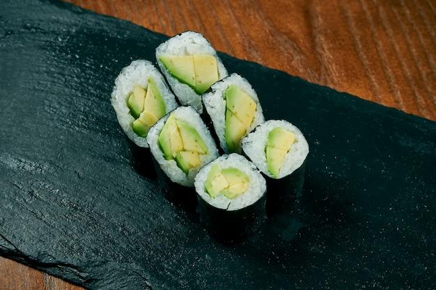 Sushi maki roule à l'avocat sur une planche en ardoise noire sur une table en bois. cuisine japonaise.
