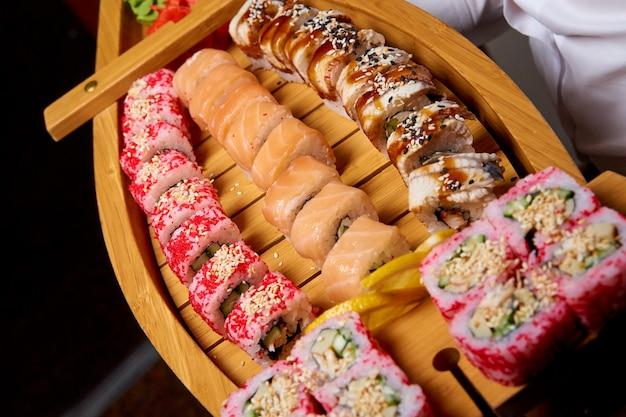 Sushi mis sur un bateau en bois dans les mains du cuisinier.