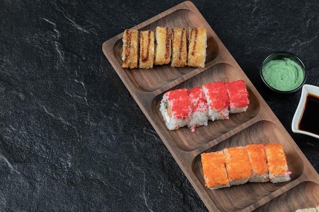 Sushi mixte sur une planche de bois avec sauce soja de côté.