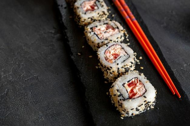 Sushi de mousse de viande de crabe japonais sur une planche en pierre avec des baguettes