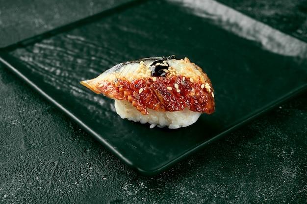 Sushi nigiri à l'anguille sur un tableau noir avec du gingembre et du wasabi. cuisine japonaise. livraison de nourriture. fond noir