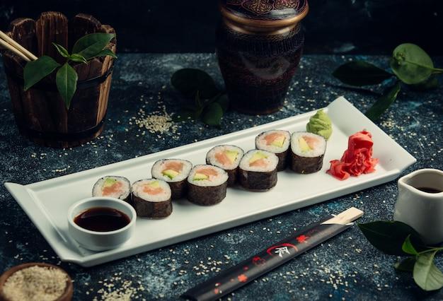 Sushi nori à l'intérieur d'un plateau blanc avec sauce soja et gingembre, wasabi.