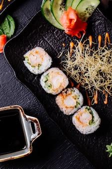 Sushi nori avec sauce de soja à l'intérieur de la plaque noire.