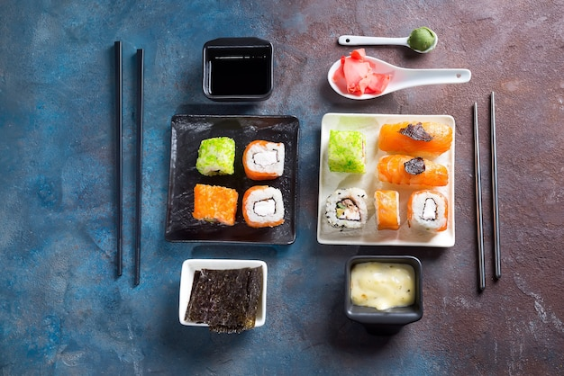 Sushi, petits pains, baguettes, sauce soja sur surface ardoise bichromie