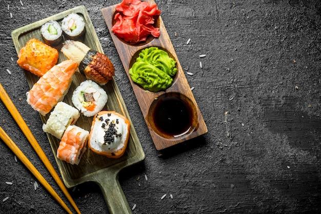 Sushi, petits pains et maki sur la planche à découper avec des baguettes et des sauces sur table rustique