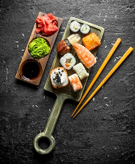 Sushi, petits pains et makis sur la planche à découper avec des baguettes et des sauces. sur fond rustique noir