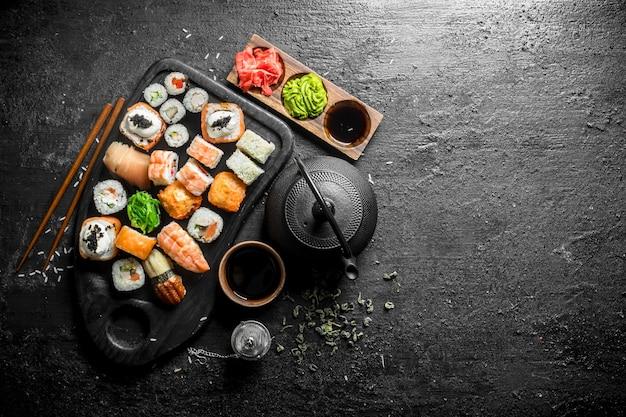 Sushi, petits pains et makis avec sauce soja, gingembre et thé vert.