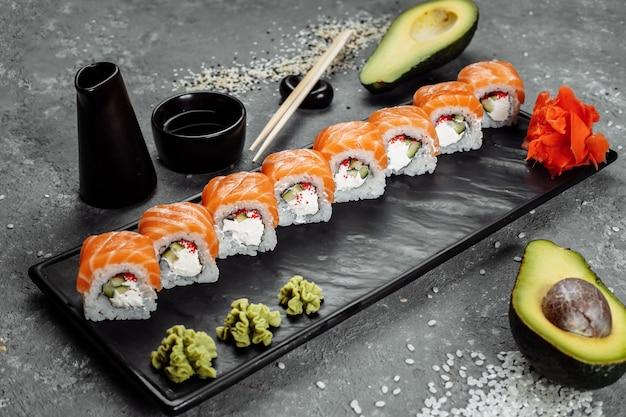Sushi philadelphia sur une plaque décorative en pierre.