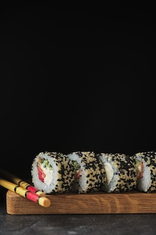 Sushi sur une planche de bois. rouleaux de poisson sur fond sombre.