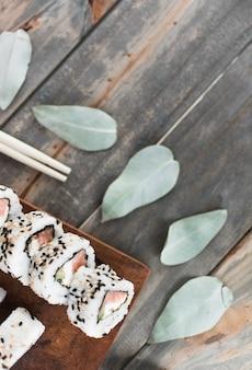 Sushi sur un plateau en bois avec des feuilles et des baguettes sur une table en bois