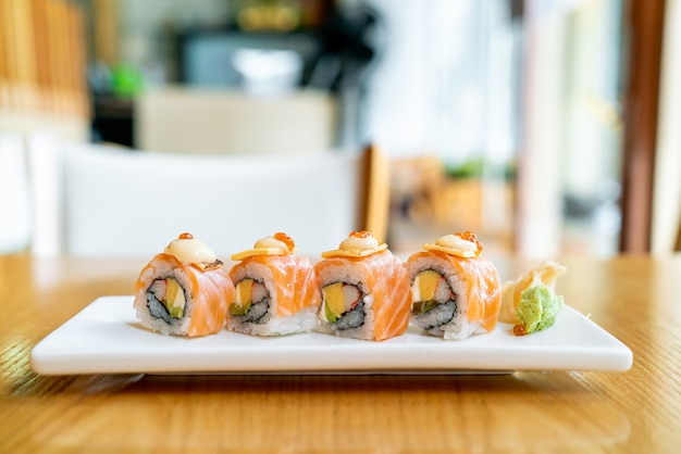 Sushi roll au saumon avec du fromage sur le dessus - style de cuisine japonaise