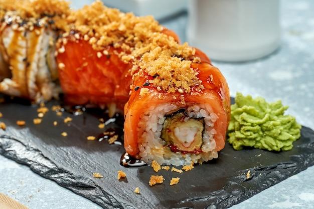 Sushi roll philadelphie avec saumon, crevettes et anguille sur une plaque noire sur fond clair