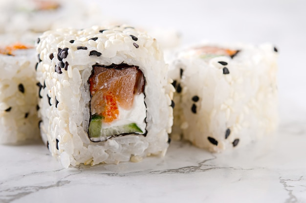 Sushi roll sushi au saumon, concombre, fromage à la crème, graines de sésame sur une table en marbre blanc.