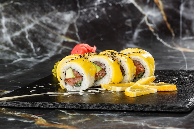 Sushi rolls avec saumon, avocat, omelette à l'intérieur et mangue sur le dessus. rouleaux de sushi au saumon sur fond de marbre noir. menu de sushi. nourriture japonaise. photo horizontale.
