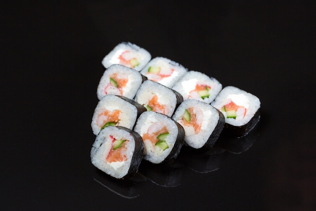 Sushi roule futo maki sur fond noir.