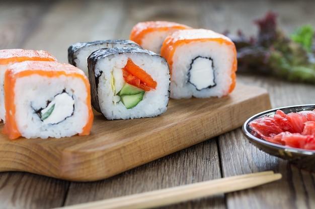 Sushi roule sur une planche à découper avec du gingembre et des herbes. bois naturel