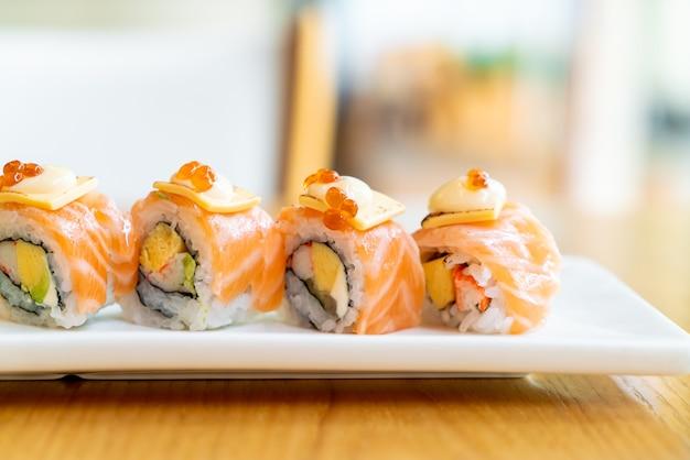 Sushi de rouleau de saumon avec du fromage sur le dessus - style de cuisine japonaise