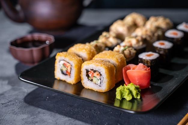 Sushi et rouleau de sushi sur table en pierre noire vue de dessus