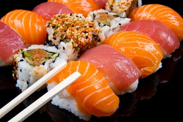 Sushi et rouleaux sur fond noir