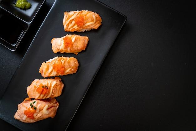 Sushi de saumon grillé sur plaque noire
