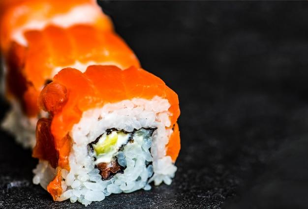 Sushi set sashimi et rouleaux de sushi servis sur ardoise en pierre