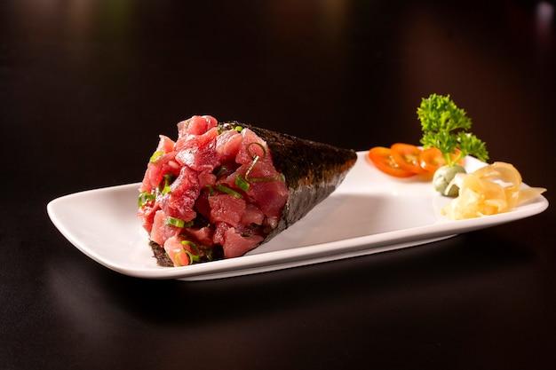 Sushi temaki de thon dans une assiette blanche sur fond noir