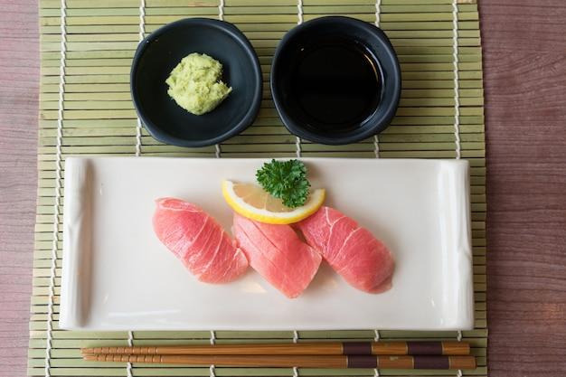 Sushi de thon otoro sur assiette blanche avec sauce japonaise et décor de feuilles vertes